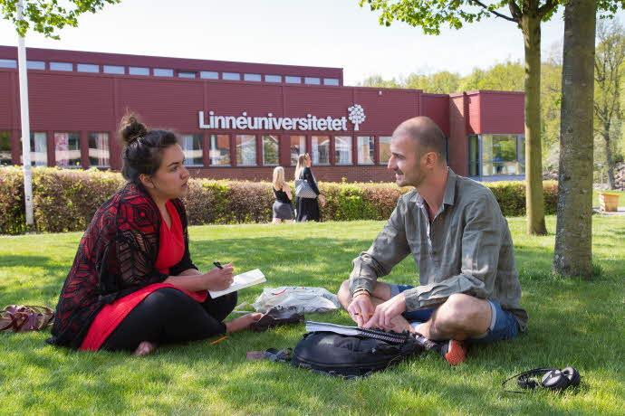 Två studenter sitter i gräset utanför huvudbyggnaden på Växjö campus