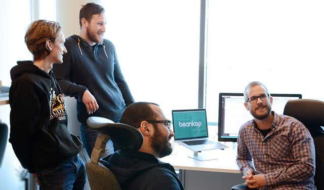 Gruppbild anställda Beanloop, Peter Persson i kontorstol framför dator