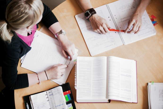 Detaljbild ovanifrån på studenter som sitter vid ett bord och pluggar med block och pennor