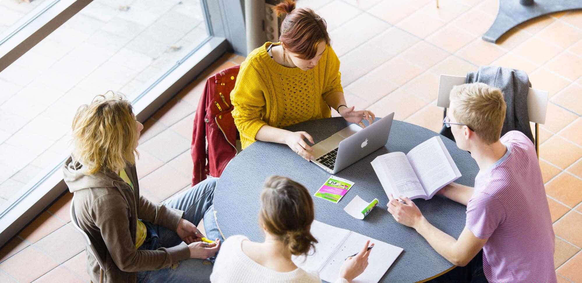 studenter som sitter vid ett bord och pluggar vid dator och i böcker