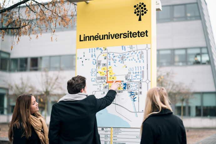 Studenter pekar på Lnu-skylt med kart aöver Växjö campus