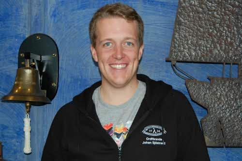 Johan står bakom en blå vägg med en skeppsklocka